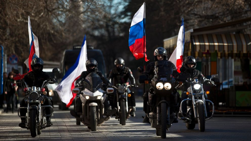 People on motorcycles decorated with Russian and Crimean flags drive in front of a van transporting the coffins  of Ukrainian soldier Sergey Kokurin, 35, and Russian Cossack militiaman Ruslan Kazakov, 34, during their funeral in Simferopol, Crimea, Saturday, March 22, 2014.