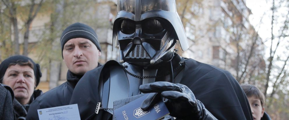 PHOTO: Darth Vader, previously known as Viktor Shevchenko, the leader of the Ukrainian Internet Party, holds up his Ukrainian passport and a certificate of candidacy for the parliamentary election at a polling station in Kiev, Ukraine, Oct. 26, 2014.