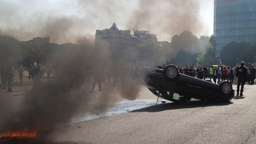 Striking taxi drivers stand behind an overthrown car during a taxi drivers demonstration, June 25, 2015, in Paris.