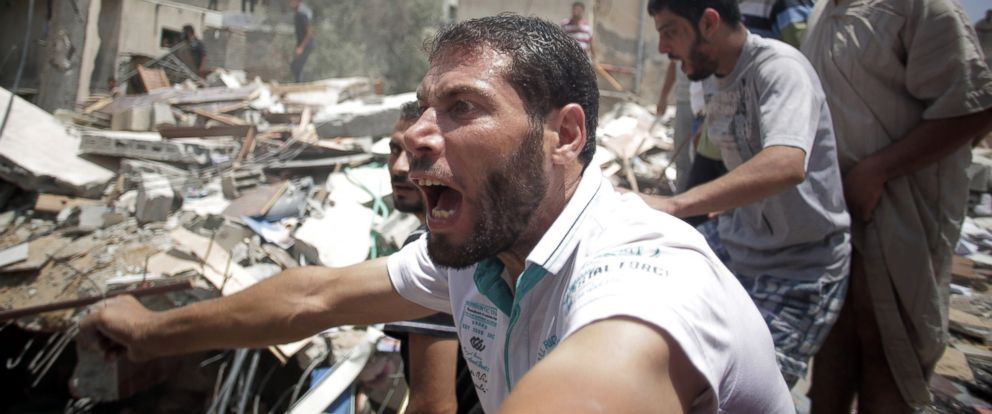 PHOTO: A Palestinian overcome by emotion watches rescuers carry a body from the rubble of a house which was destroyed by an Israeli missile strike, in Gaza City, July 21, 2014.