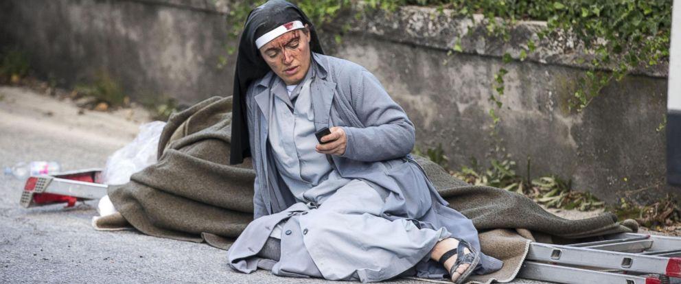 PHOTO: A nun checks her mobile phone as she lies near a ladder following an earthquake in Amatrice, Italy, Aug. 24, 2016.