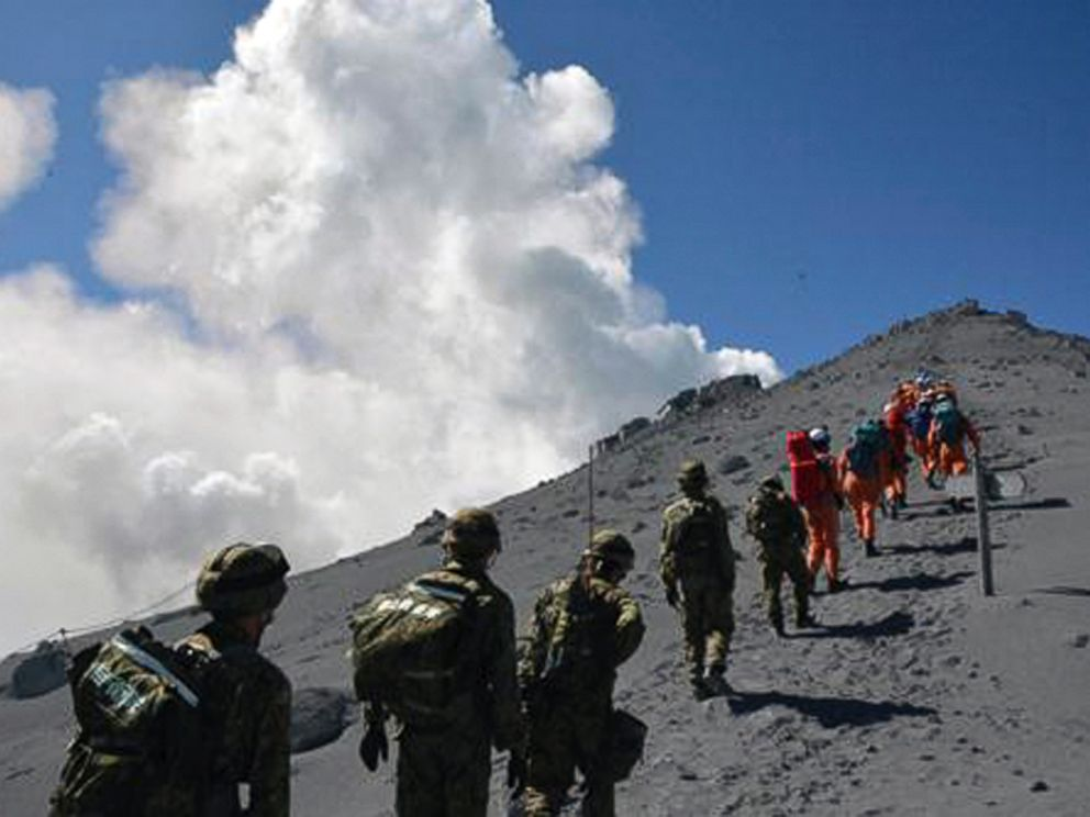 PHOTO: JGSDF personnel and fire fighters head for the summit of Mount Ontake to rescue people who have been trapped in the mountaintop lodge one day after the volcano became active in central Japan, Sept. 28, 2014.