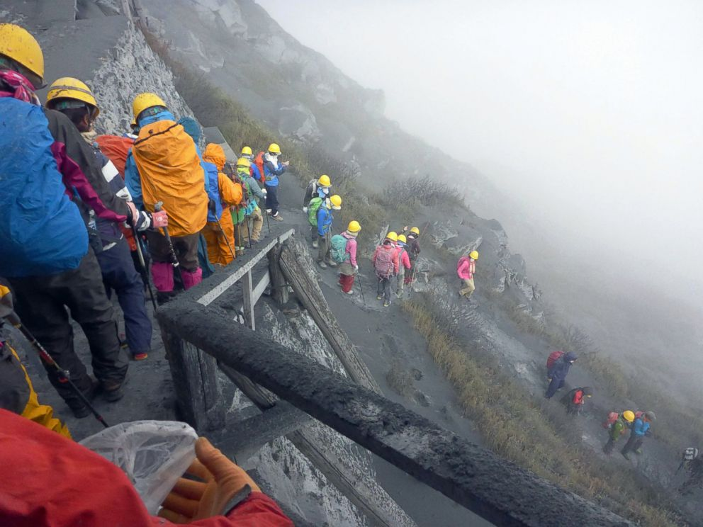 PHOTO: Climbers descend Mt. Ontake to flee as the volcanic mountain erupts in central Japan, Saturday, Sept. 27, 2014.