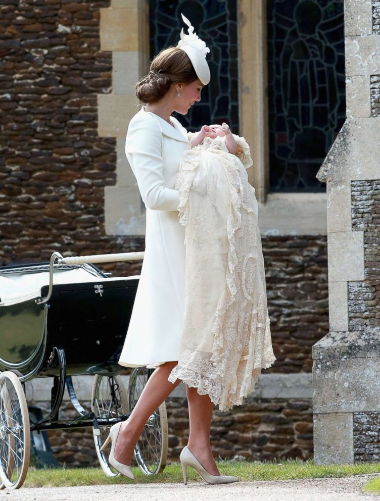 PHOTO: Britains Kate the Duchess of Cambridge carries Princess Charlotte after taking her out of a pram as they arrive for Charlottes Christening at St. Mary Magdalene Church in Sandringham, England, July 5, 2015.