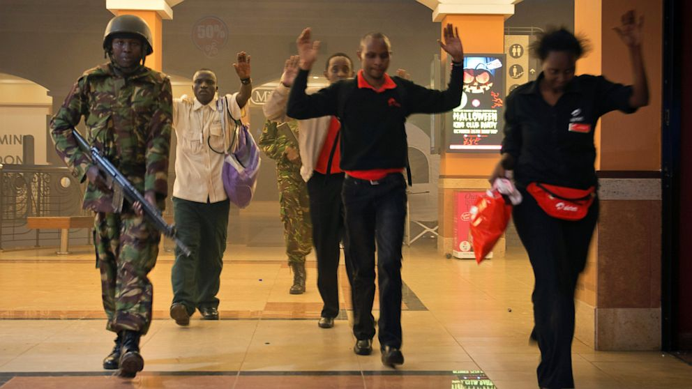Kenya Civilians who had been hiding during a gun battle hold their hands in the air as a precautionary measure before being searched by armed police leading them to safety, inside the Westgate Mall, Sept. 21, 2013.