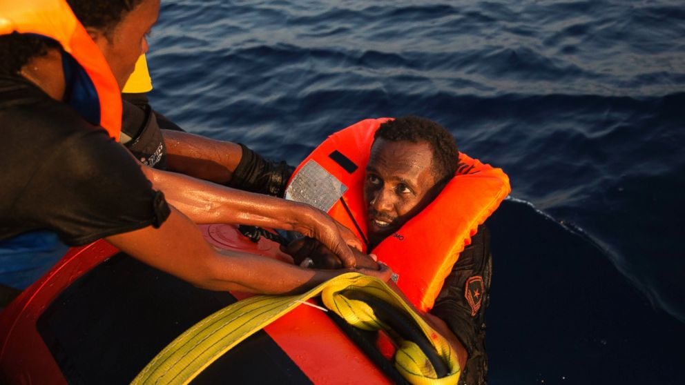 A migrant from Eritrea is helped after jumping into the water from a crowded wooden boat during a rescue operation in the Mediterranean sea, Aug. 29, 2016.