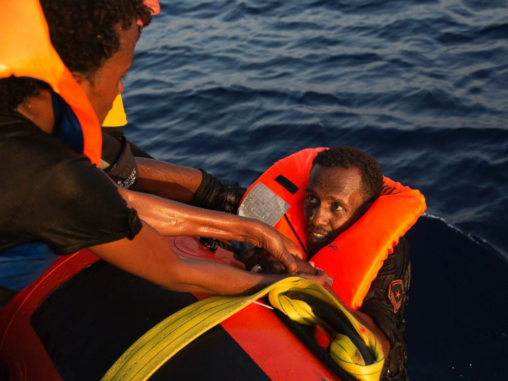 PHOTO: A migrant from Eritrea is helped after jumping into the water from a crowded wooden boat during a rescue operation in the Mediterranean sea, Aug. 29, 2016.