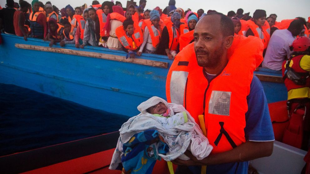 A man carries his five-day-old son after been rescued from a crowded wooden vessel as they were fleeing Libya during a rescue operation in the Mediterranean sea, Aug. 29, 2016.