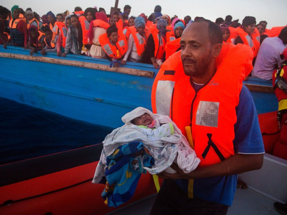 PHOTO: A man carries his five-day-old son after been rescued from a crowded wooden vessel as they were fleeing Libya during a rescue operation in the Mediterranean sea, Aug. 29, 2016.