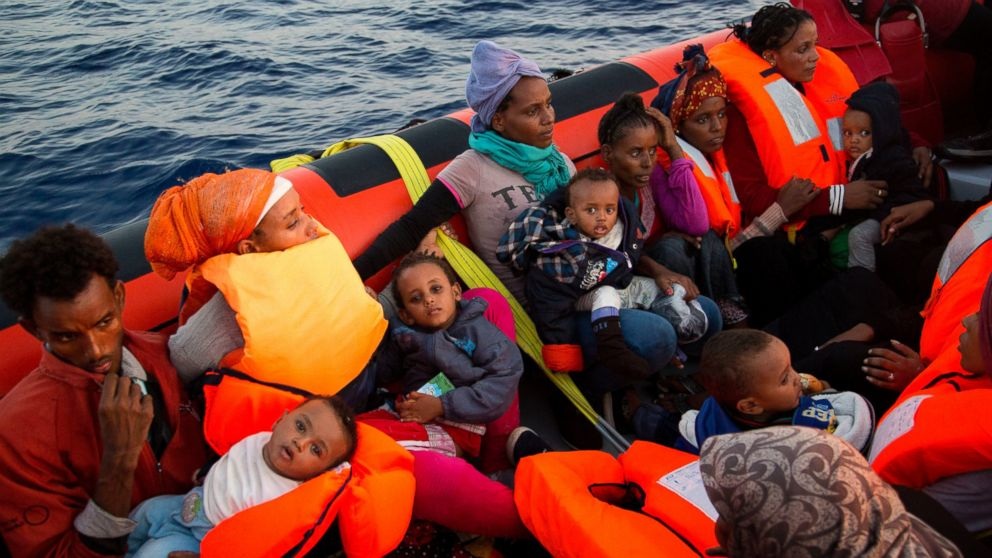 Migrants from Eritrea hold their children after been rescued from a crowded wooden boat as they were fleeing Libya, about 13 miles north of Sabratha, Libya, Aug. 29, 2016.
