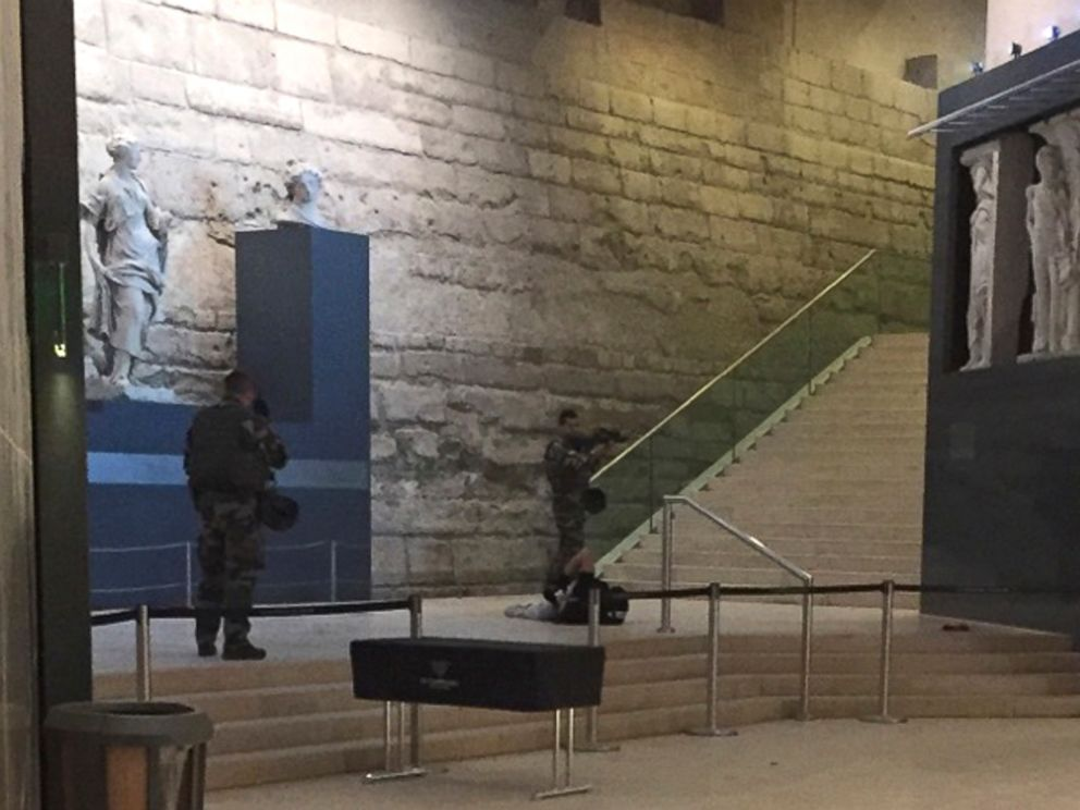 PHOTO: The body of a man lays on the floor as two soldiers guard him in the Louvre museum, Feb. 3, 2017 in Paris.