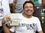 PHOTO: Italian Luigi Maraldi, left, shows his passport as he reports himself to Thai police Lt. Gen. Panya Mamen, right, at Phuket police station in Phuket province, southern Thailand Sunday, March 9, 2014.