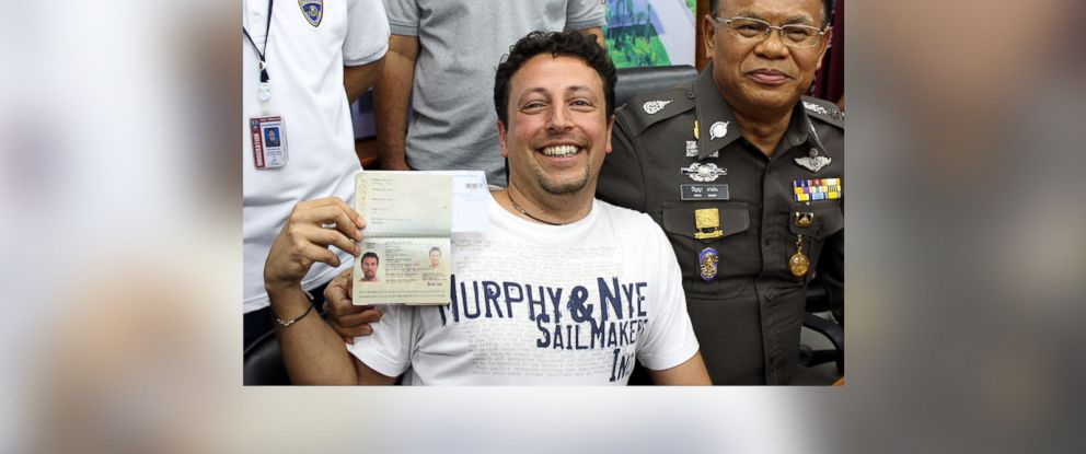 PHOTO: Italian Luigi Maraldi, left, shows his passport as he reports himself to Thai police Lt. Gen. Panya Mamen, right, at Phuket police station in Phuket province, southern Thailand Sunday, March 9, 2014.