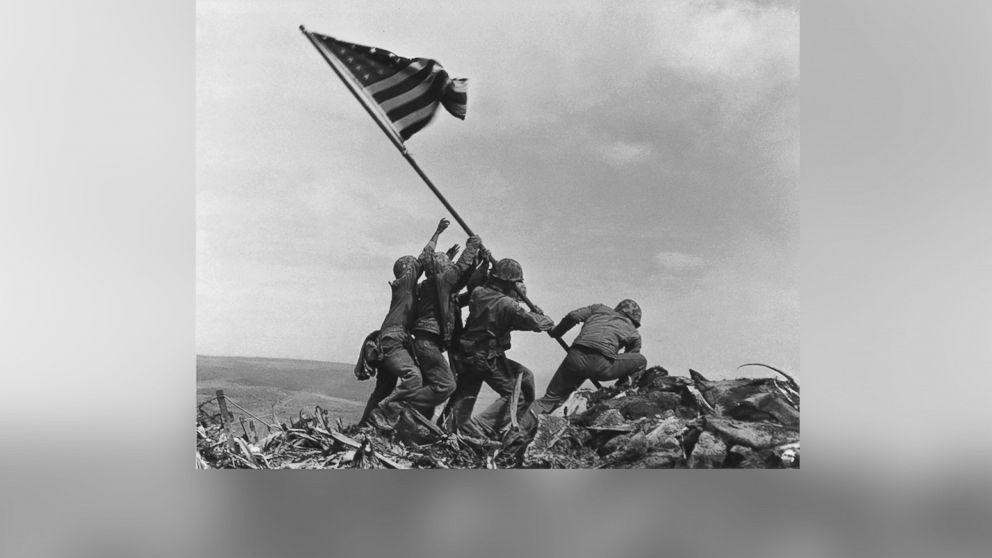 U.S. Marines of the 28th Regiment, 5th Division, raise the American flag atop Mt. Suribachi in Iwo Jima, Japan, Feb. 23, 1945.