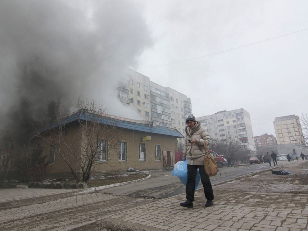 PHOTO: A woman resident passes by a burning house in Mariupol, Ukraine, Saturday, Jan. 24, 2015.