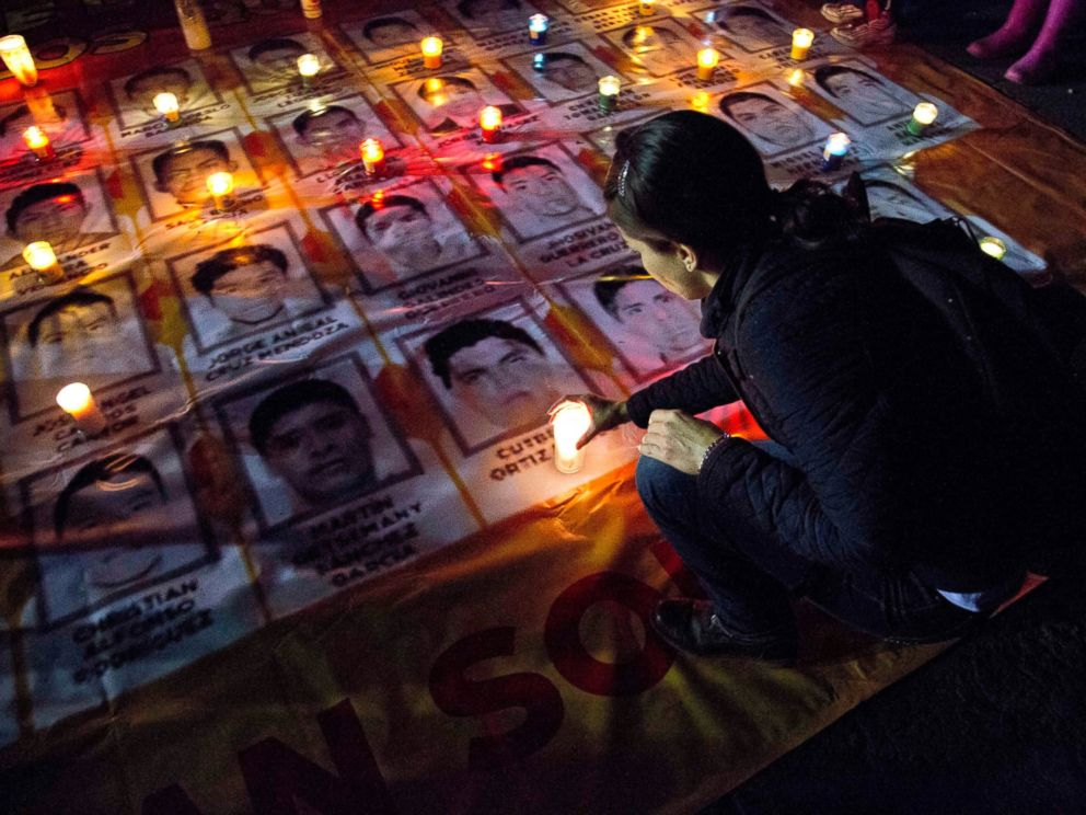 PHOTO: A woman places a candle on photos of the missing students during a protest against the disappearance of 43 students from the Isidro Burgos rural teachers college, in Mexico City, Oct. 22, 2014.
