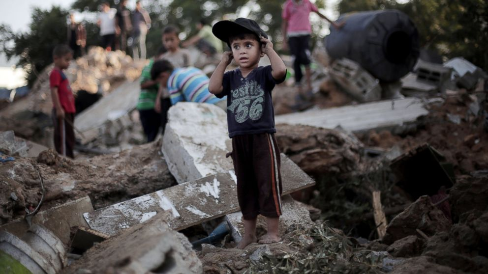 A Palestinian boy stands in the rubble of a destroyed house the day after an Israeli strike in the town of Beit Hanoun, Gaza Strip, July 9, 2014.