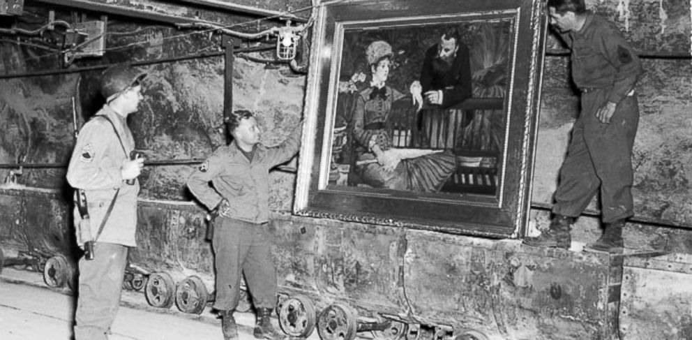 """PHOTO: In this April 25, 1945 image released by the U.S. National Archives, U.S. Army personnel stand by a painting called, """"Wintergarden,"""" by French impressionist Edouard Manet, which was discovered in the vault in Merkers, Germany."""