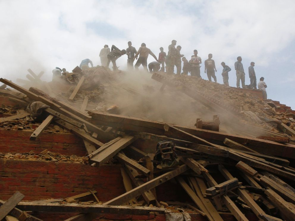 PHOTO: Volunteers help remove debris of a building that collapsed at Durbar Square, after an earthquake in Kathmandu, Nepal, Saturday, April 25, 2015.