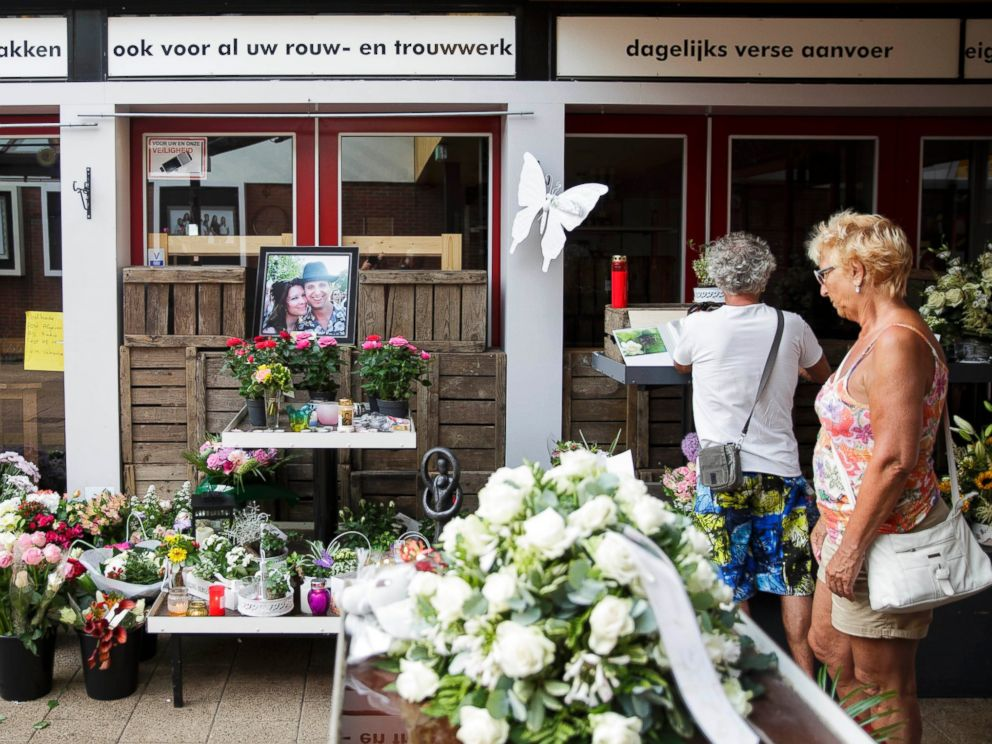 PHOTO: Women stand near a portrait of Neeltje Tol, left, and Cor Schilder, right, placed with flowers and candles in front of their flower shop in Volendam, Netherlands, July 19, 2014.