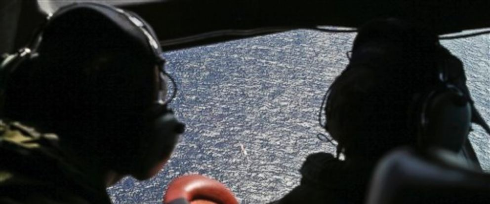 PHOTO: Wing commander Rob Shearer captain of the Royal New Zealand Air Force P3 Orion left, and Sgt. Sean Donaldson look out the cockpit windows during search operations for missing Malaysia Airlines Flight MH370 in the southern Indian Ocean.