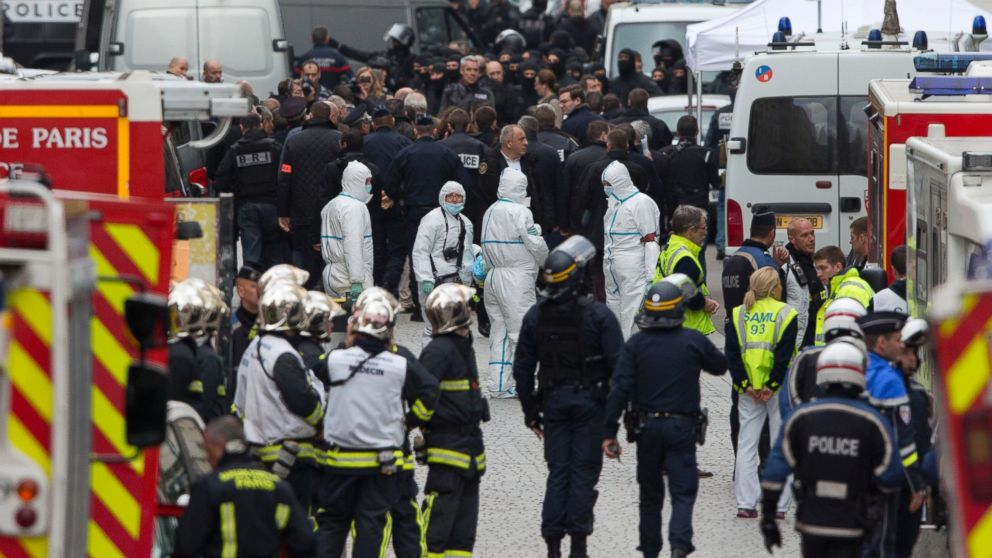 Forensic experts in white suits wait for a go ahead after an operation of security forces against a group of extremists in Saint Denis, near Paris, Nov. 18, 2015.