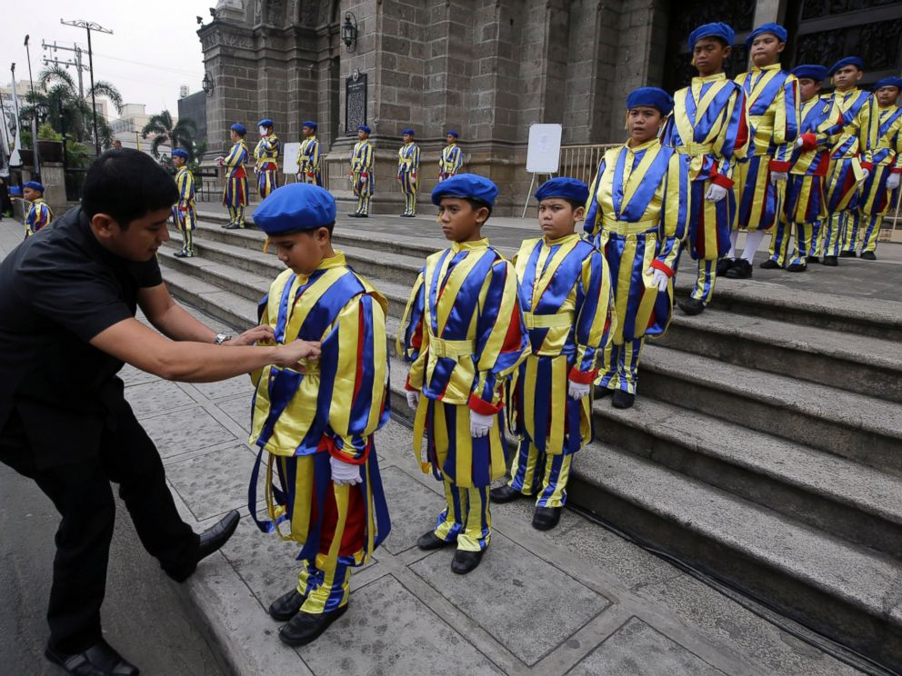 PHOTO: A Catholic priest adjusts the uniform of boys who are dressed as Vatican Swiss guards during a rehearsal for the visit of Pope Francis outside the Manila Cathedral, Jan. 14, 2015 in Manila, Philippines.