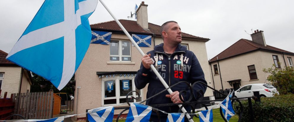 PHOTO: Yes activist Darren Brander holds a Saltire flag outside his home in Glasgow, Scotland, as the campaign ahead of the Scottish independence referendum enters its final days, Sept. 15, 2014.