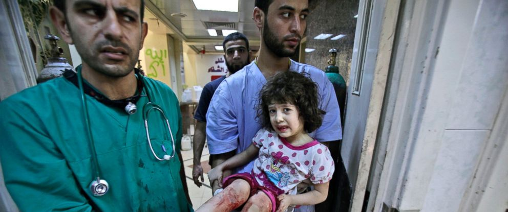 PHOTO: Medics carry Fatima Qassim, 6, who was badly injured in her legs after government forces fired on her familys car, to the emergency room in a hospital in Aleppo, Syria, Sept. 11, 2012.