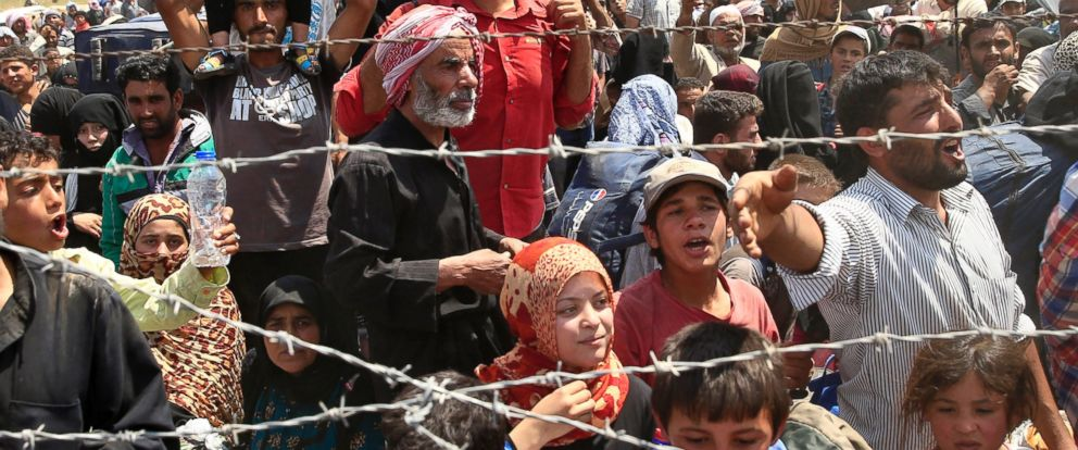 PHOTO: Syrian refugees gather at the Turkish border as they flee intense fighting in northern Syria between Kurdish fighters and Islamic State militants in Akcakale, Turkey, June 15, 2015.