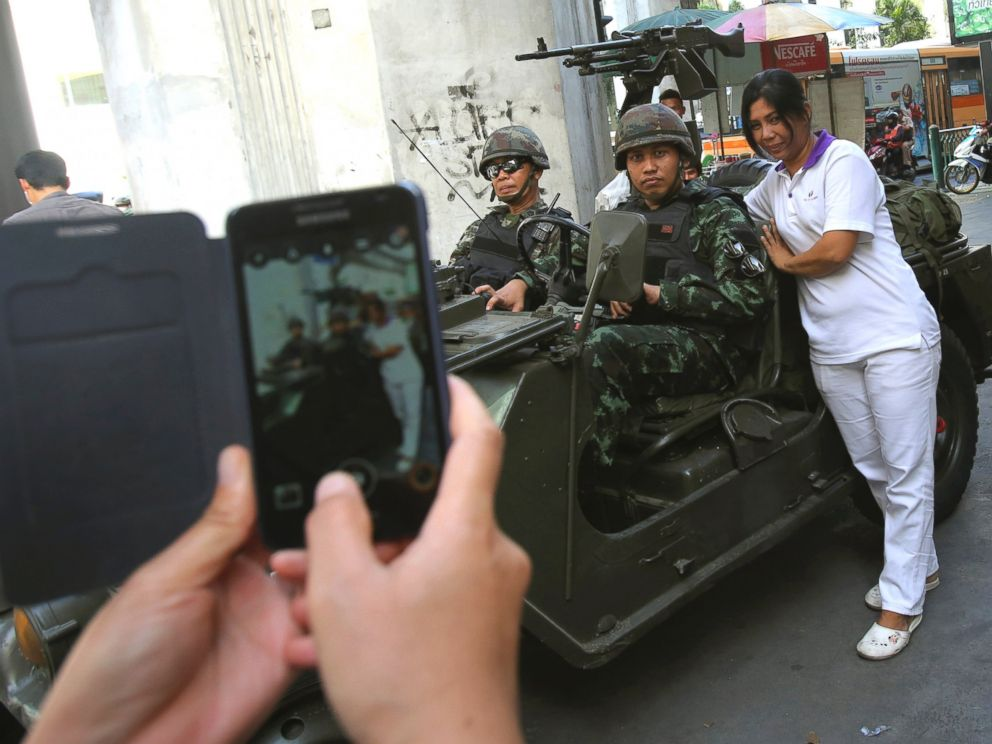 PHOTO: A Thai woman take pictures with Thai soldiers stationed outside the Thai police headquarters, May 20, 2014, in Bangkok.