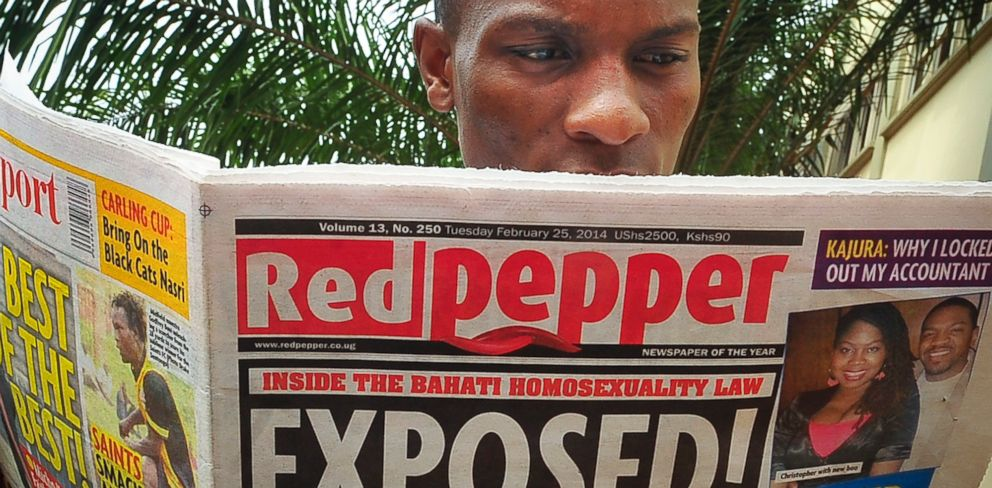 "PHOTO: A Ugandan reads a copy of the ""Red Pepper"" tabloid newspaper in Kampala, Uganda, Feb. 25, 2014."