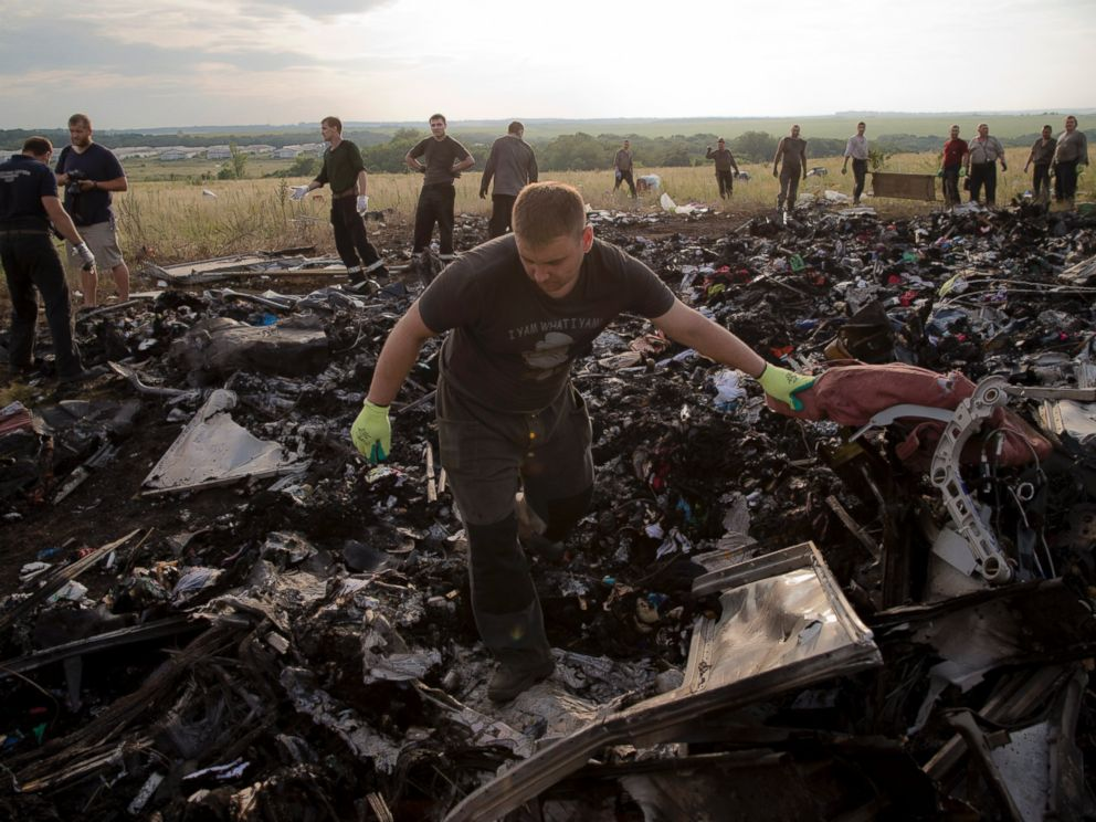 PHOTO: A man looks for the remains of victims in the debris at the crash site of Malaysia Airlines Flight 17 near the village of Hrabove, eastern Ukraine, July 19, 2014.