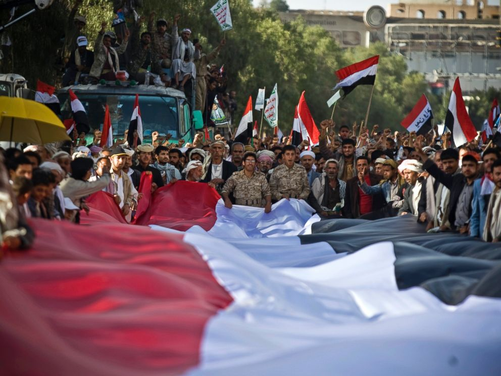 PHOTO: Houthi Shiite Yemenis hold carry a large representation of the national flag during a celebration marking the fourth anniversary of the revolution in Sanaa, Yemen, Feb. 11, 2015.