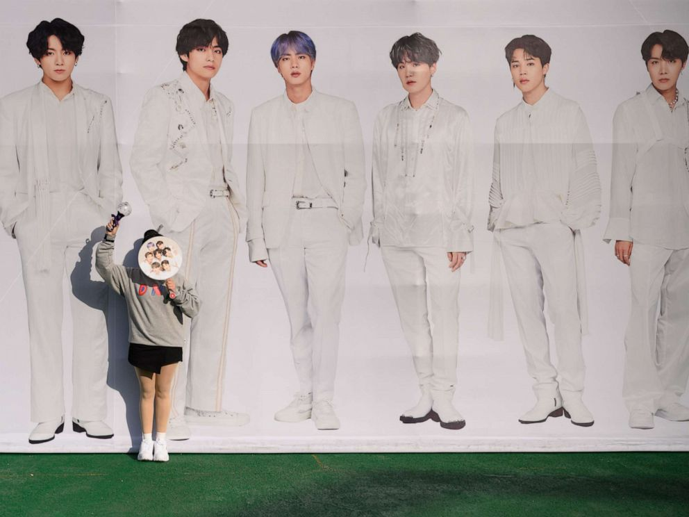 PHOTO: In a photo taken on October 29, 2019, a fan of BTS poses against a backdrop featuring an image of the band members, as they arrive for the final concert of their world tour at the Olympic stadium in Seoul. (Photo by ED JONES/AFP via Getty Images)