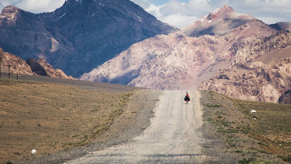 A traveler on the M41 road (also called Pamir highway), crossing the Pamir plateau in Tajikistan.