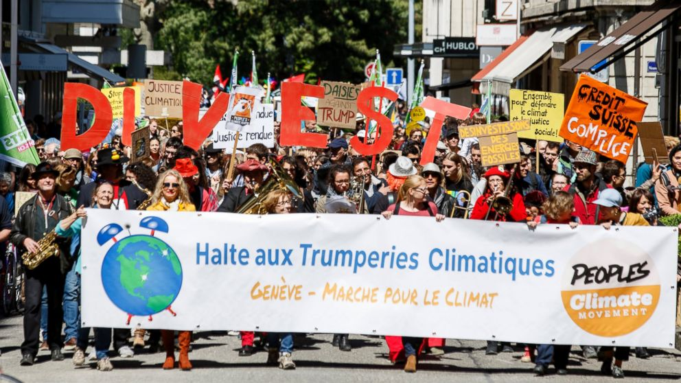 """About five hundred protesters hold placards reading, """"Stop climactic Trumperies"""" during the World Climate March in Geneva, Switzerland, April 29, 2017."""