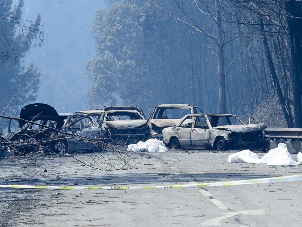 PHOTO: Burnt cars and body bags are seen on the N236 road between Figueiro dos Vinhos and Castanheira de Pera, near Pedrogao Grande, central Portugal, June 18, 2017.