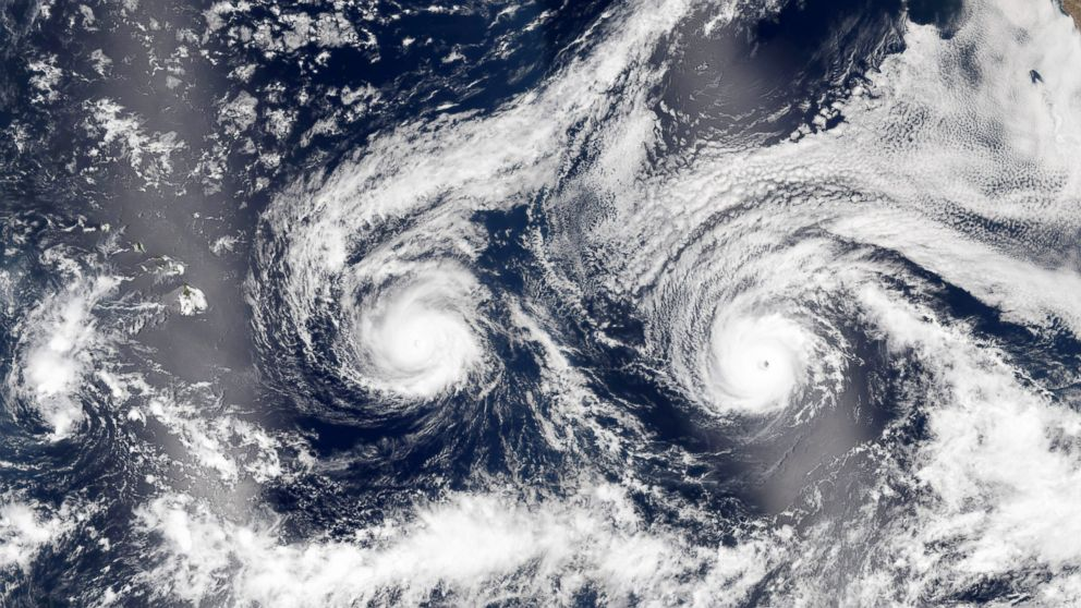 A handout image released by NASA Earth Observatory on Aug. 31, 2016 shows a satellite image of hurricanes Madeline (L) and Lester (R) over the Pacific Sea near Hawaii.