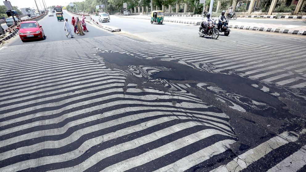 Road markings appear distorted as the asphalt starts to melt due to the high temperature in New Delhi, May 27, 2015.