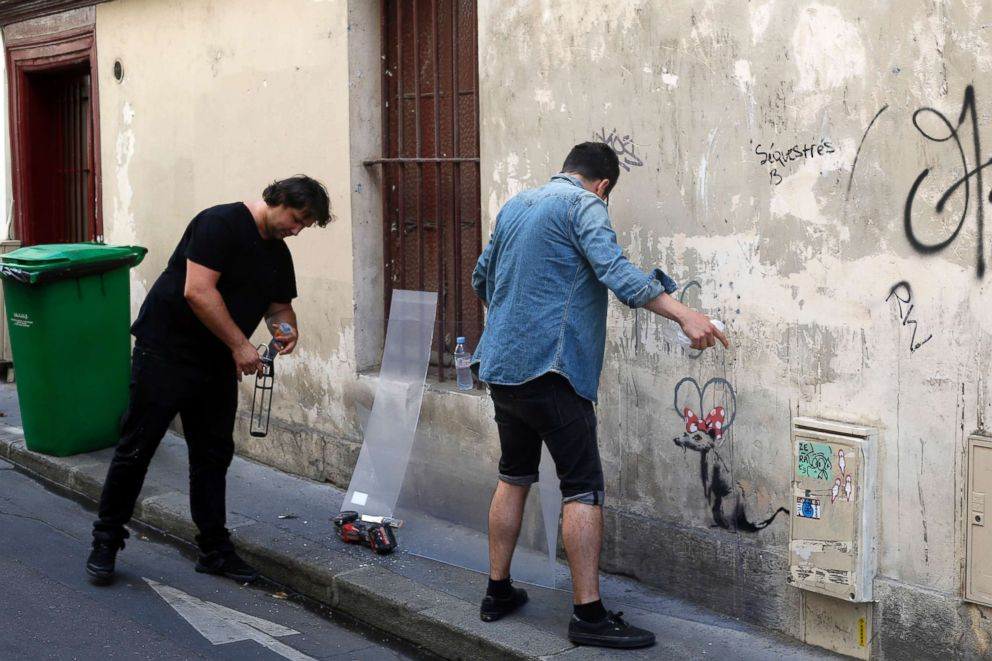 PHOTO: Two men place a protective board over a graffiti believed to be attributed to street artist Banksy, in Paris, on June 25, 2018.