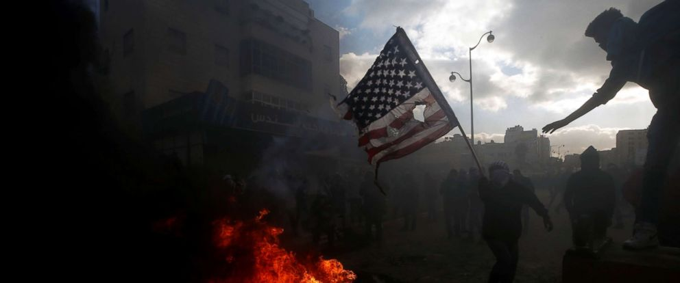 PHOTO: A Palestinian protester prepares to burn a U.S. flag during clashes with Israeli troops at a protest against U.S. President Donald Trumps decision to recognize Jerusalem as the capital of Israel, Dec. 7, 2017.