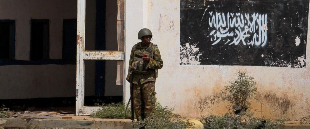 PHOTO: A soldier of the Kenyan Contingent serving with the African Union Mission in Somalia (AMISOM) stands near the black flag of the Al Qaeda linked group Al Shabaab painted on the wall of Kismayo Airport, Oct. 2, 2012 in this handout photo.