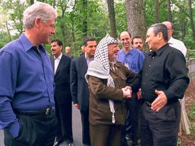 PHOTO: President Bill Clinton looks on while Palestinian leader Yasser Arafat and Israeli Prime Minister Ehud Barak shake hands on the opening day of the Mid-East peace talks July 11, 2000 at Camp David MD.