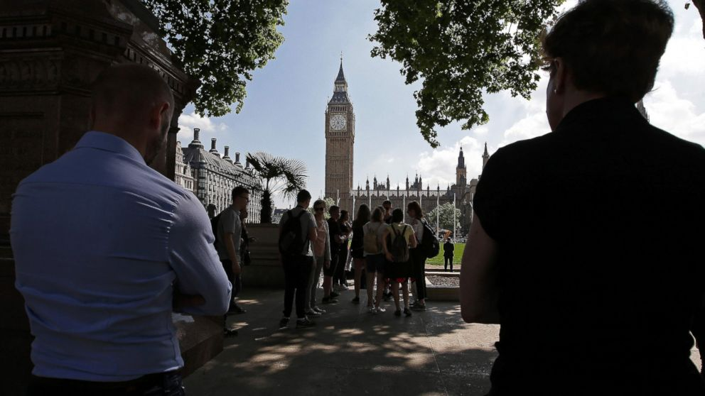 People stop to observe a minute's silence in Parliament Square, Westminster in central London, on May 25, 2017, as a mark of respect to the victims of the May 22 terror attack at the Manchester Arena.