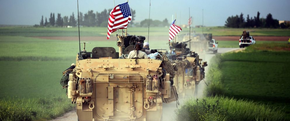 PHOTO: U.S. forces, accompanied by Kurdish Peoples Protection Units (YPG) fighters, drive their armored vehicles near the northern Syrian village of Darbasiyah, on the border with Turkey, on April 28, 2017.