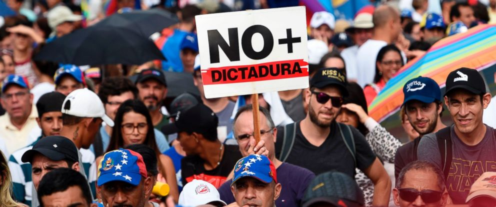 "PHOTO: Venezuelan opposition activists, one holding a sign which translates to ""No Dictatorship"" take part in a rally against the government of President Nicolas Maduro, in Caracas, on May 18, 2017."
