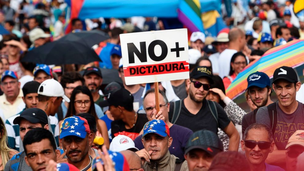 """Venezuelan opposition activists, one holding a sign which translates to """"No Dictatorship"""" take part in a rally against the government of President Nicolas Maduro, in Caracas, on May 18, 2017."""