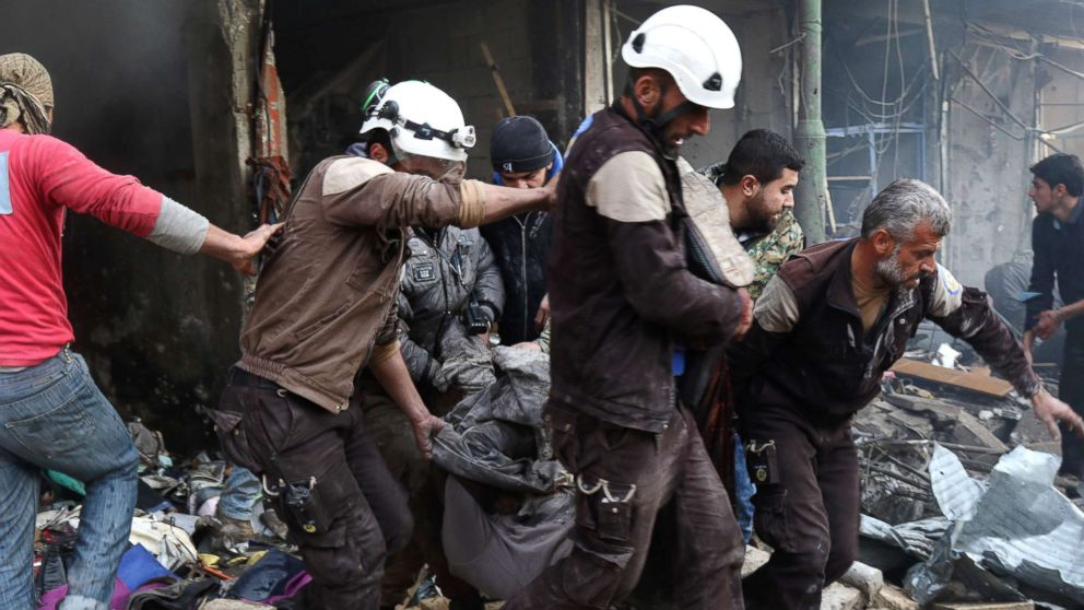 Syrian men and Civil Defense volunteers, also known as the White Helmets, evacuating a victim from a building following an air strike on the village of Maaret al-Numan, in the country's northern province of Idlib, Dec. 4, 2016.