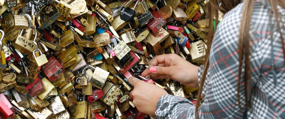 """PHOTO: A tourist fixes a love Padlocks on the """"Pont des arts,"""" May 31, 2015, in Paris, France."""